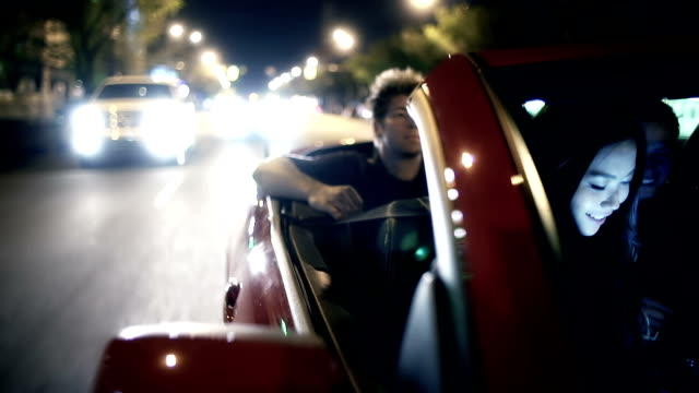 Young adults ride in convertible car at night.