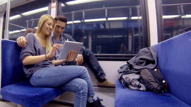 vidéos et rushes de jeunes adultes prendre le métro et en jouant avec une tablette - boyfriend