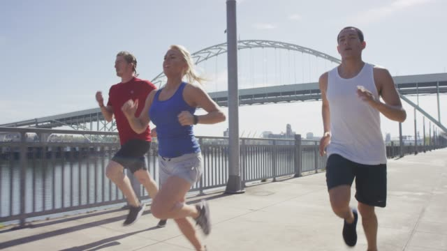 Young Adults Running Along River in City