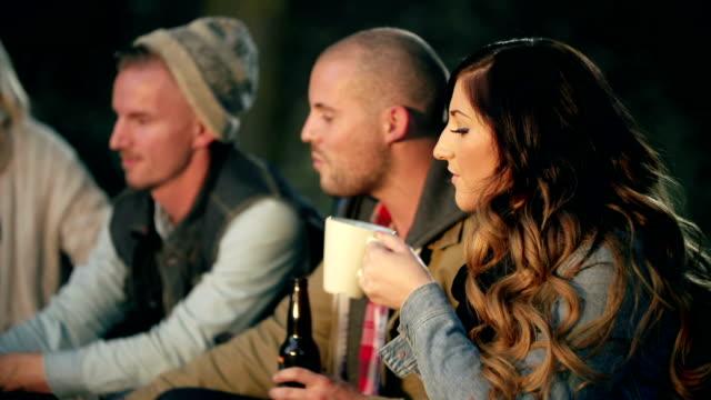 Giovani adulti seduti attorno a un fuoco di campo nella notte