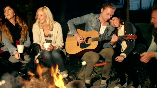 stockvideo's en b-roll-footage met young adults sit around a camp fire at night - koffie drank