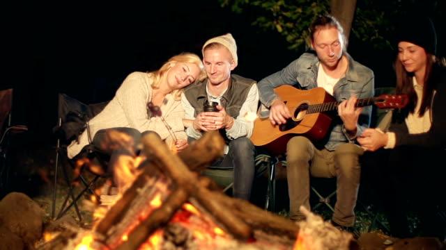 vídeos y material grabado en eventos de stock de adultos jóvenes sentarse alrededor de una camp fire por la noche - hoguera de campamento