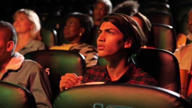 vídeos de stock e filmes b-roll de young adults sits in movie theatre, close up - audiência