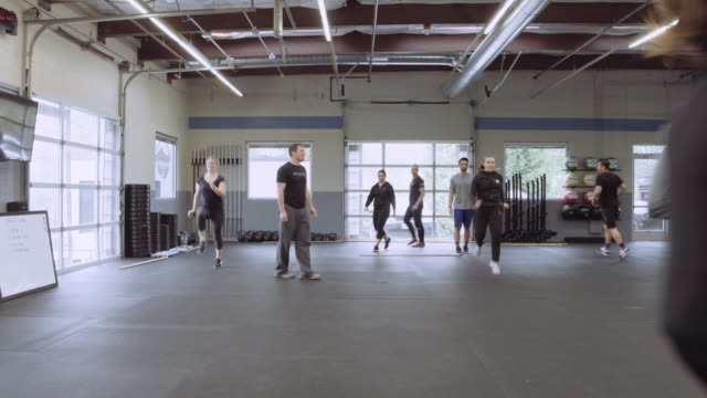 Young adults warming up with high knees exercise
