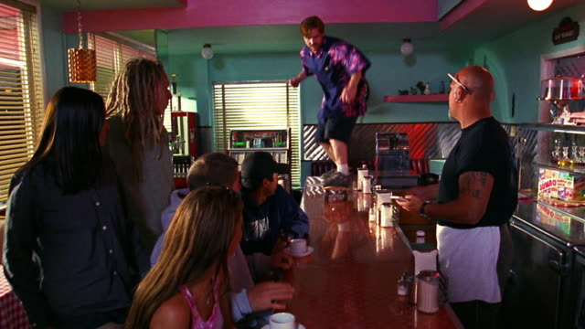 young adults watching skateboarder skate on counter to camera in diner / waiter behind counter - bizarre stock videos & royalty-free footage