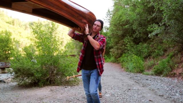 junge erwachsene mit einem kanu in der wildnis - carrying stock-videos und b-roll-filmmaterial