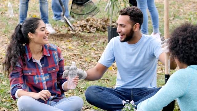 junge erwachsenen zusammenarbeiten, während der verschönerung gemeinschaftsprojekt - gärtnern stock-videos und b-roll-filmmaterial