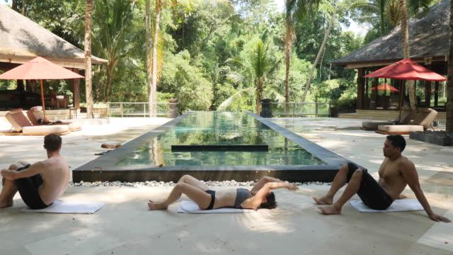 若い大人のプールの横にワークアウト - リゾート地点の映像素材/bロール