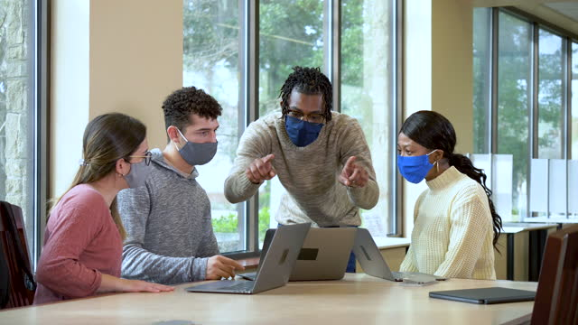 young adults working together on laptops, wearing masks - university student stock videos & royalty-free footage