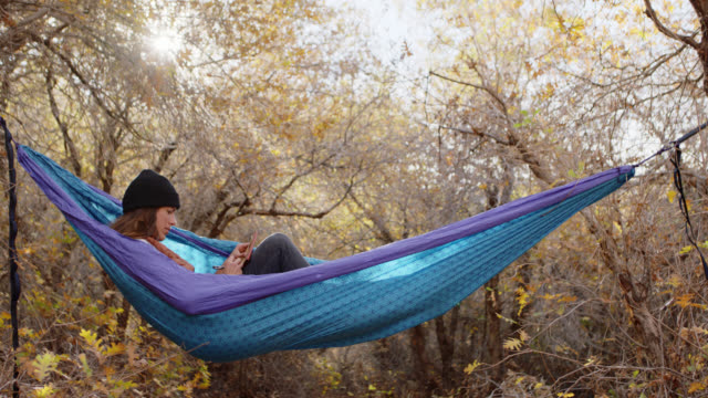 young adventurous woman rocks in hammock and writes in journal in the great outdoors. - equipment点の映像素材/bロール
