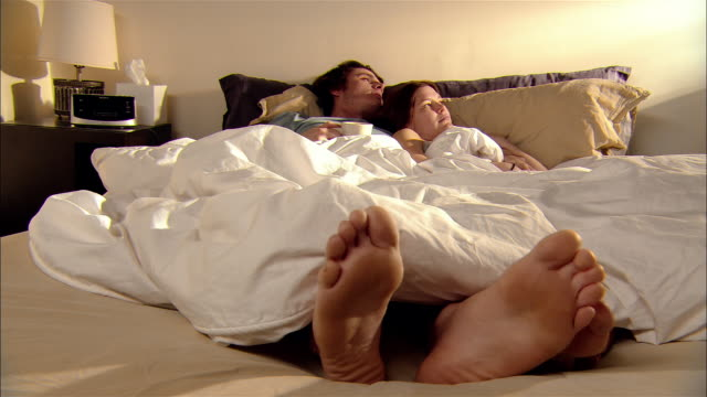 young affectionate couple lying in bed - duvet stock videos & royalty-free footage