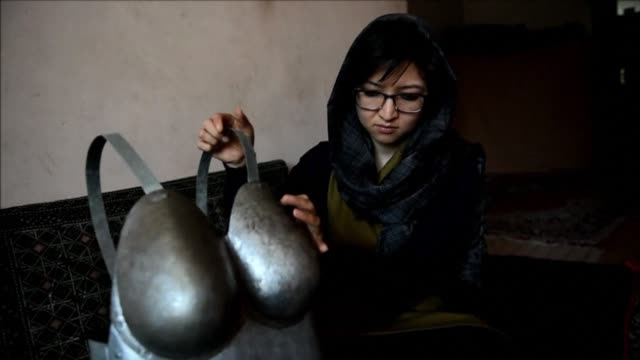 a young afghan artist who walked through the streets of kabul wearing a suit of armour featuring large breasts and buttocks in protest against sexual... - suit of armour stock videos and b-roll footage