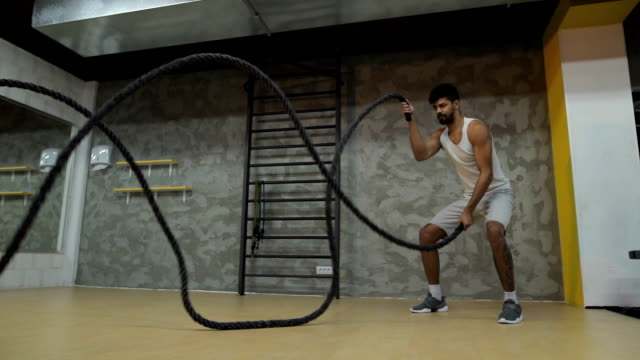 Young African American athlete doing battle ropes exercise in a gym. Slow motion.