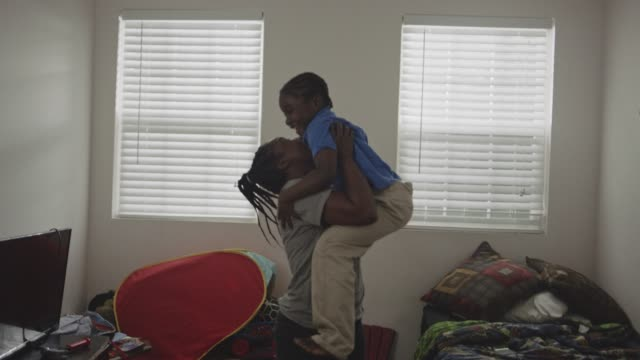 young african american boy jumps off of bed into mother‰۪s waiting arms and embraces her. - mother stock videos & royalty-free footage