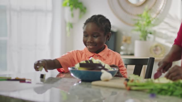 young african american boy makes an oops face as he helps mom in the kitchen. - mistake stock videos & royalty-free footage