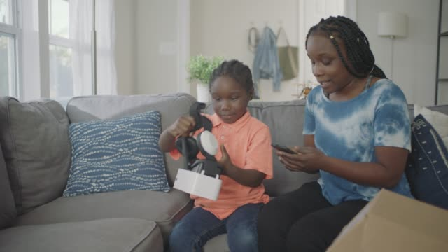 young african american boy opens package to reveal virtual reality headset and excitedly puts it on. - birthday gift stock videos & royalty-free footage