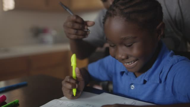 vídeos de stock, filmes e b-roll de cu. young african american boy practices writing and drawing shapes as his proud mother watches and encourages him. - mãe solteira