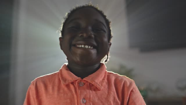 cu slo mo. young african american boy stands in front of flickering projector lights and smiles at camera. - imagination stock-videos und b-roll-filmmaterial