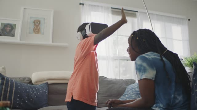 young african american boy wearing vr headset reaches out hand and looks around in wonder. - mother stock videos & royalty-free footage