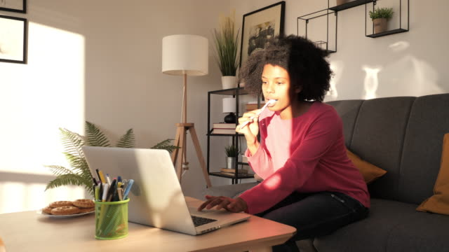 young african american businesswoman brushing teeth and checking emails at home - toothbrush stock videos & royalty-free footage