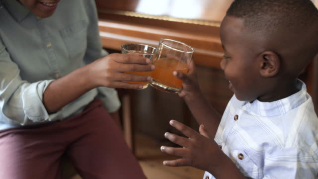 young african american child cheers cups, close up - drinking glass stock videos & royalty-free footage