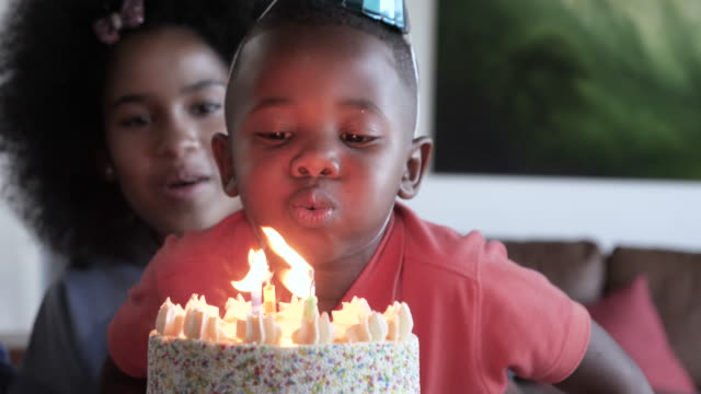 young african american children blows out candles during birthday party, close up - birthday cake stock videos & royalty-free footage