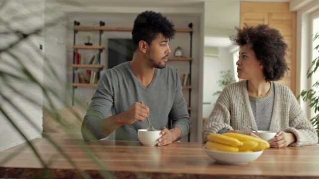 Young African American couple having a conversation during breakfast time at home.
