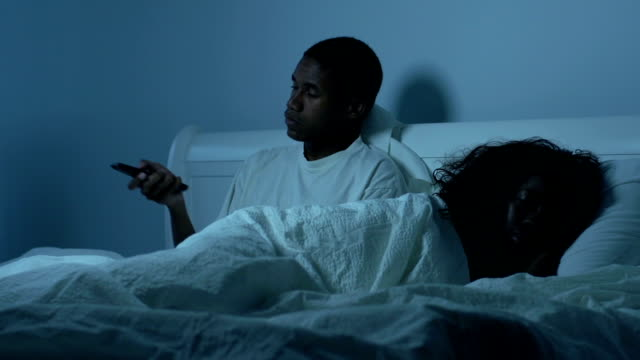 Young African American couple in bed with TV