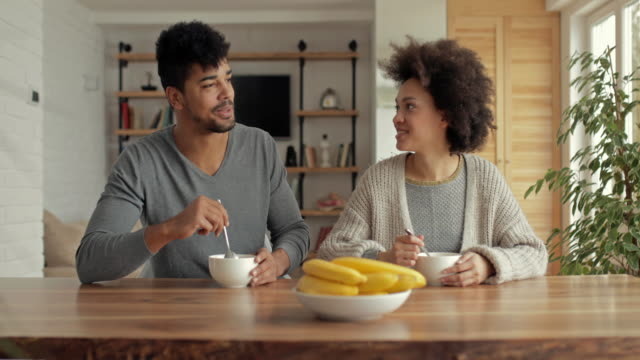Young African American couple talking while eating at dining table.