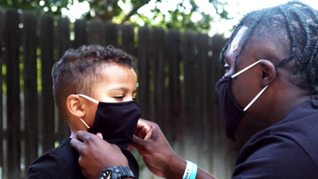 young african american dad helping his three-year-old mixed race son place his personal protection mask on his face in defense against the spread of the covid-19 coronavirus pandemic - offspring stock videos & royalty-free footage
