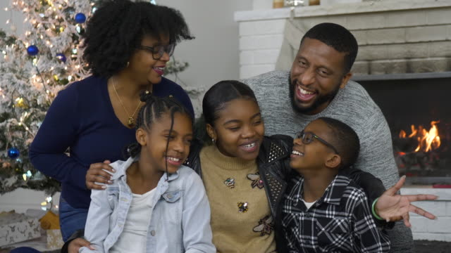 a young african american family hugging and laughing on christmas morning together - tree hugging stock videos & royalty-free footage
