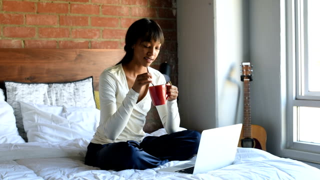 Young African American female in Bed with Coffee and Laptop