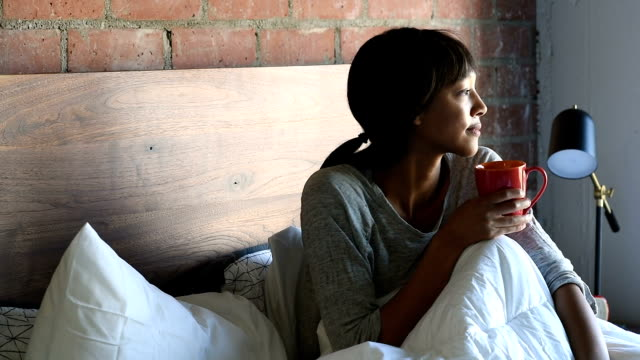 Young African American female in Bed with Coffee