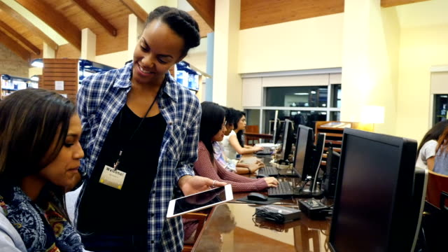 a young african american female librarian assists college or high school student in library computer lab - librarian stock videos & royalty-free footage