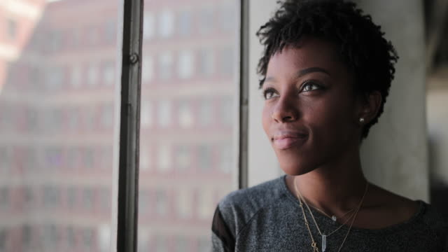 vidéos et rushes de young african american female looking out of window in loft apartment thinking - niveau d'éducation