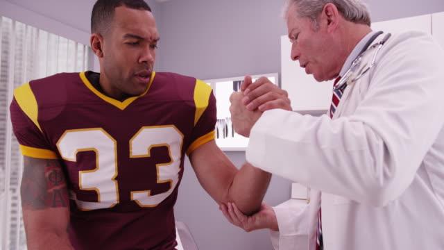 vídeos de stock, filmes e b-roll de young african american football player having doctor examine arm - physical injury