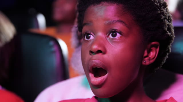 young african american girl eats popcorn in movie theatre, close up - sorpresa video stock e b–roll
