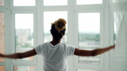 Young African American girl is walking to the window at home and parting the curtains then enjoying view from the window. Housing, people and lifestyle concept.