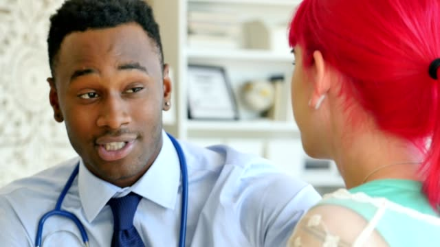 young african american male doctor discusses diagnosis with a female patient - pink hair stock videos and b-roll footage