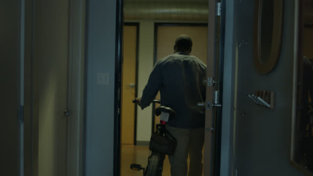 vídeos de stock e filmes b-roll de young african american man grabs his keys and walks out the door of his city apartment with his bicycle. - environmental conservation