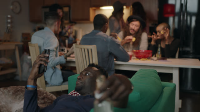 young african american man looks at smartphone and sips a beer on the couch while friends hang out around the kitchen table in the background. - party social event video stock e b–roll
