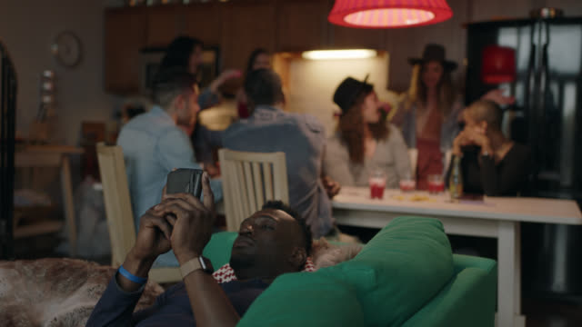 young african american man looks at smartphone on the couch while friends hang out around the kitchen table in the background. - fashionable stock videos & royalty-free footage