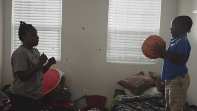 young african american mother and son toss basketball back and forth in bedroom and collapse onto bed laughing. - ausrutscher stock-videos und b-roll-filmmaterial