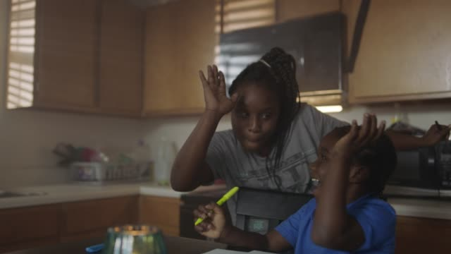 SLO MO. Young African American mother gives son a high five as she helps him with homework at kitchen table.