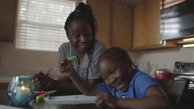 SLO MO. Young African American mother makes son laugh as she helps him with homework at kitchen table.
