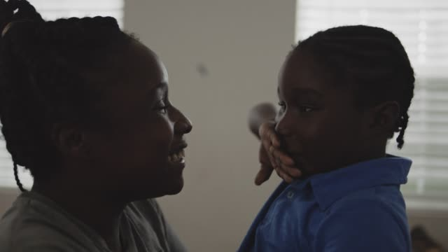cu slo mo. young african american mother showers son with kisses as he wipes them away and tries to escape. - boys stock videos & royalty-free footage