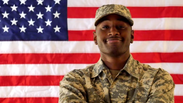 young african american soldier stands confidently in front of the american flag - uniform stock videos & royalty-free footage