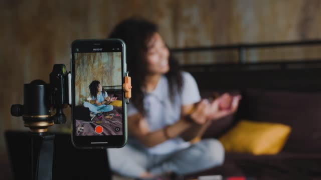 Young african american woman make up blogger streaming live with a smartphone reviewing make up products while sitting on her bed at home, dolly shot