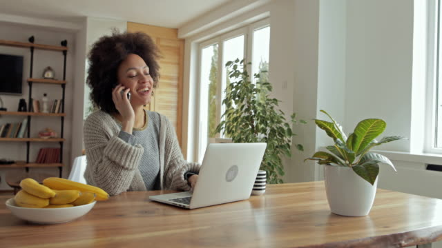 young african american woman typing an e-mail on laptop and answering a phone call. - usare il telefono video stock e b–roll