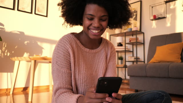 vidéos et rushes de jeune femme afro-américaine utilisant des sites de rencontres en ligne pour trouver le match parfait - jeunes femmes